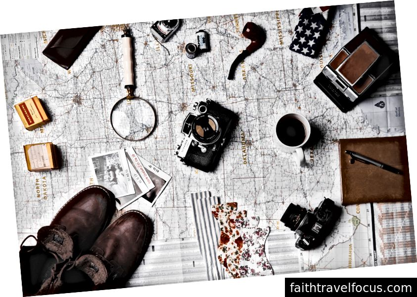 """Unsplash'ta ian dooley tarafından """"Bir büyüteç düzlemi, bir fincan kahve, kameralar, fotoğraflar ve çeşitli seyahat öğeleri harita üzerinde"""" ian dooley"""