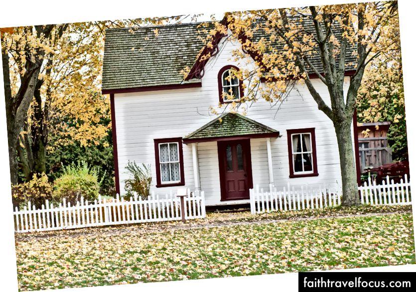 Một ngôi nhà nhỏ màu trắng được bao quanh bởi những cái cây vào mùa thu bởi Scott Webb trên Bapt