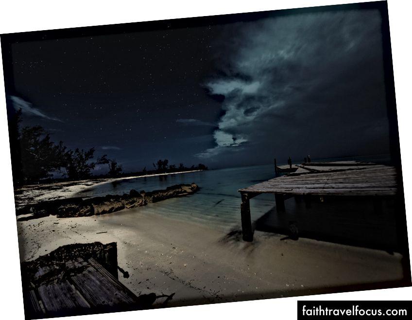 «Коричневий дерев'яний док і водойма під чорним небом у нічний час» Джеймса Звадло на Unsplash