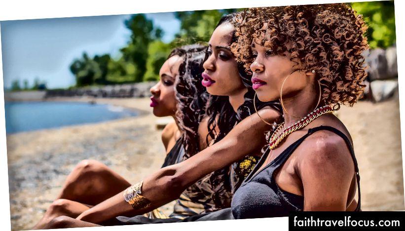 «Три жінки, що сидять на березі біля дерев вдень» Йовона Стівена на Unsplash