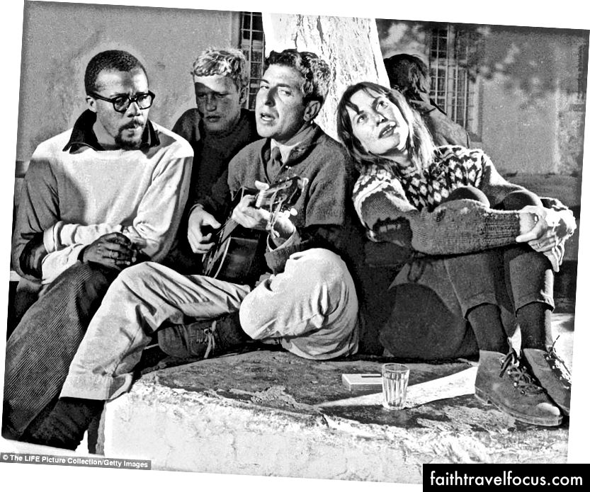 Cohen chơi guitar tại Douskos Taverna, nhiếp ảnh gia James Burke của LIFE Magazine. Charmian Clift ngồi cạnh anh ta. © Tạp chí LIFE.