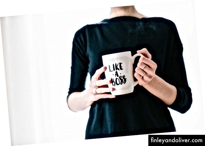 Một người phụ nữ cầm một chiếc cốc màu trắng với một người giống như một ông chủ in bản in của Brooke Lark trên.