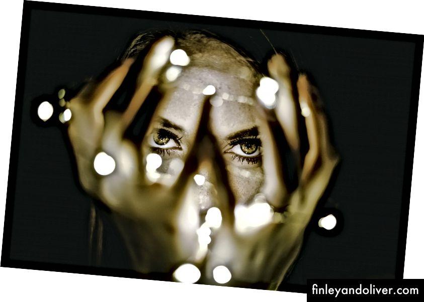 Cận cảnh một đôi mắt của người phụ nữ qua đôi tay được bao quanh bởi ánh sáng thần tiên.