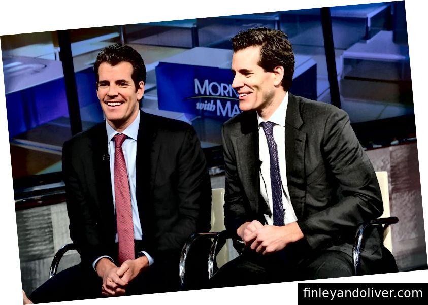 """Предприемачите Тайлър Уинклевос и Камерън Уинклевос обсъждат биткойн с Мария Бартиромо в студия FOX на 11 декември 2017 г. Първите """"биткойн милиардери"""" в света, нетните им стойности са практически идентични, но има основна причина за това. (Астрид Ставиарц / Гети Имиджис)"""