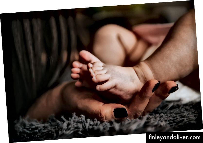 """""""Краката на бебето се държат от женска ръка с боядисани и маникюрни ръце, опиращи се в сиво одеяло"""" от Алекс Пасарелу на Unsplash"""