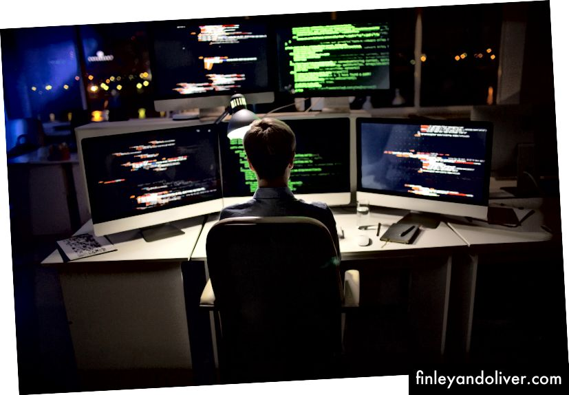 Працьовитий кодер зі стильною стрижкою, що сидить перед комп'ютером і пише код © seventyfour