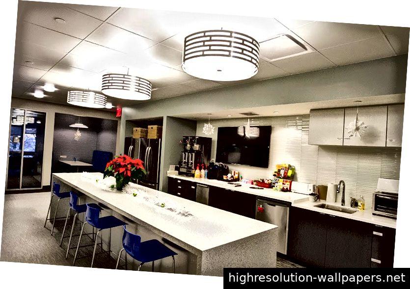 Innenansicht des Kollaborationszentrums mit einem Flachbildfernseher an der Wand der Küchenzeile, der normalerweise 24-Stunden-Weltnachrichten in den Raum sendet - Whirlpool Corporation Riverview Campus.