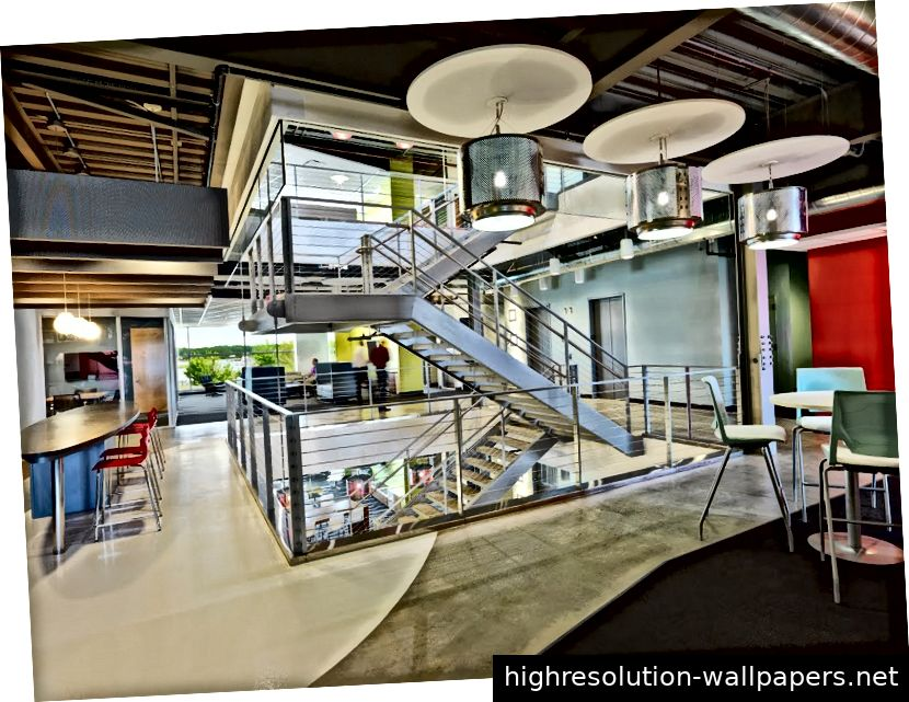 Innenansicht der Kollaborationszentren mit offenen Kollaborationsbereichen, umgeben von großen Fenstern mit Blick auf die malerischen Wasserwege darunter - Whirlpool Corporation Riverview Campus.