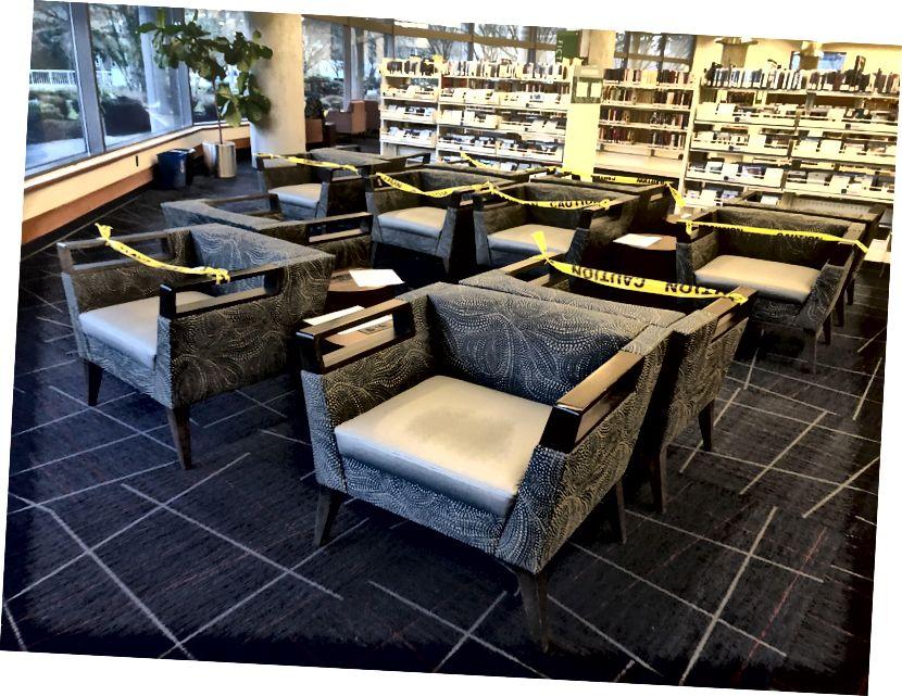 Bibliotēkā, kur es eju, ir daži krēsli ar dzeltenu lentu, lai cilvēki nesēdētu kopā