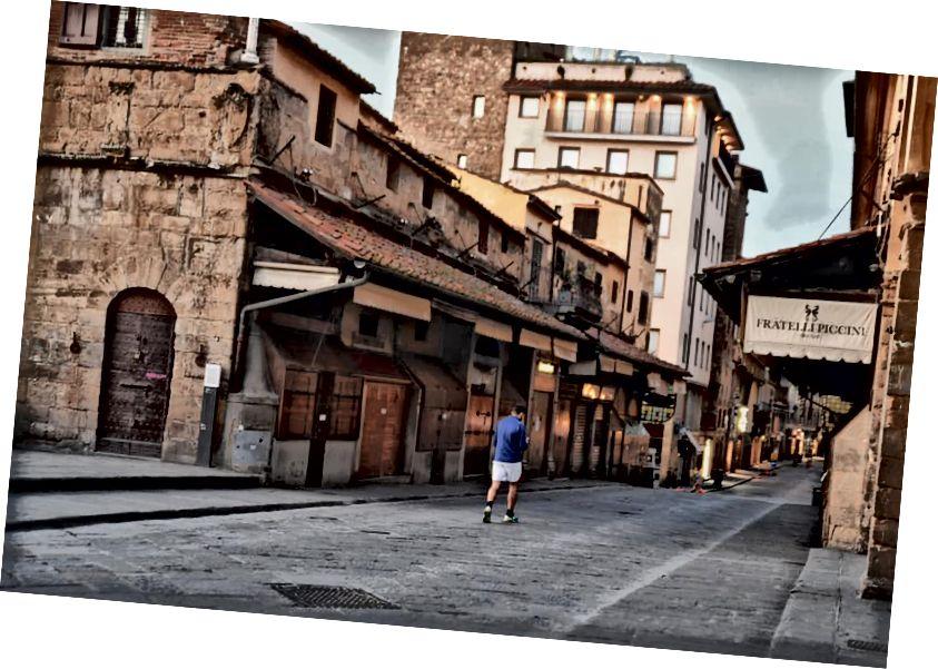 Egy ember keresztezi a redőnyös Ponte Vecchio-t a koronavírus-válság közepette.