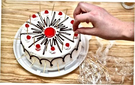 Utilitzeu escuradents per subjectar l'embolcall de plàstic per sobre d'un pastís glaçat