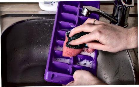 Enchendo a bandeja de cubos de gelo