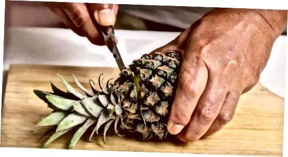 Eine Ananashälfte entkernen, während die Haut noch an ist