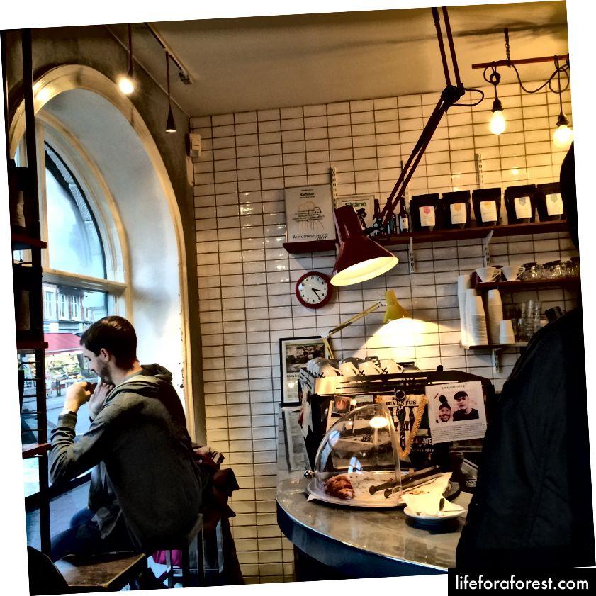 Kaffebaren pa Mollan ichkarisiga qahva olib kiring yoki tashqaridagi yorqin qizil yog'och kursilarga joylashtiring.