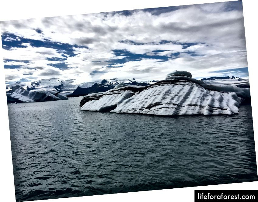 Jokulsarlonning aysbergidagi qora chiziqlar ifloslanishdan emas. Ular o'tmishdagi vulkanik otilishlar natijasida hosil bo'lgan cho'kindi qatlamlar.