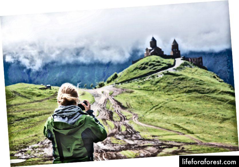 """""""Turgåer tar et fotografi av et slott på toppen av et frodig fjell"""" av Sylwia Bartyzel på Unsplash"""