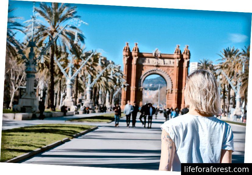 """""""Bakfra av en blond kvinne som går på en vei under en triumfbue i Barcelona"""" av Toa Heftiba på Unsplash"""