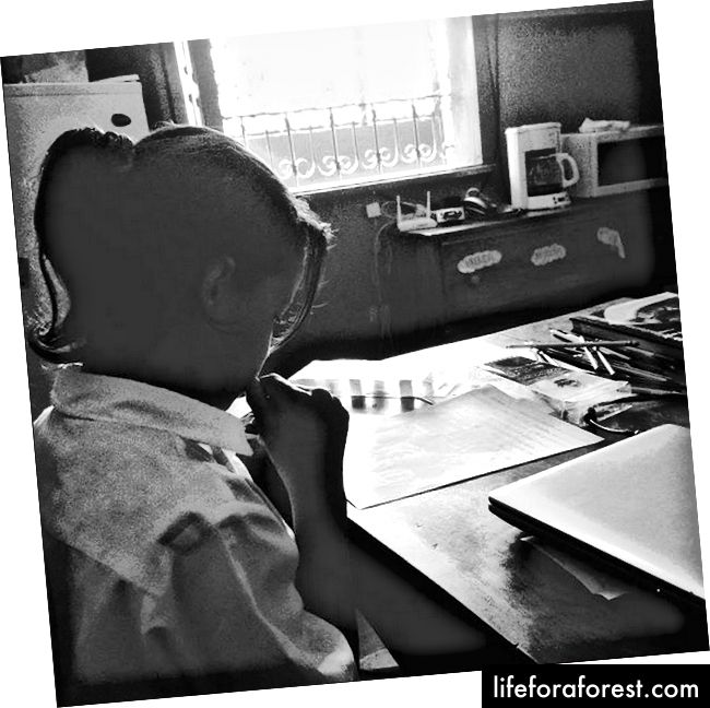 En liten jente sliter med å skrive et brev til sponsoren sin.