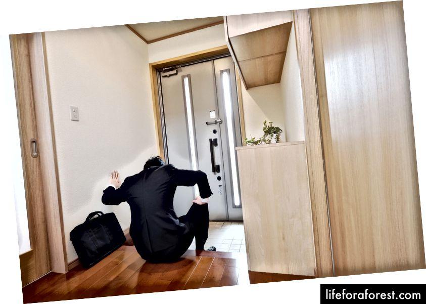 O'z uyining genkanida (kirish joyida) poyafzal almashtiradigan ishbilarmon erkak © Akoji