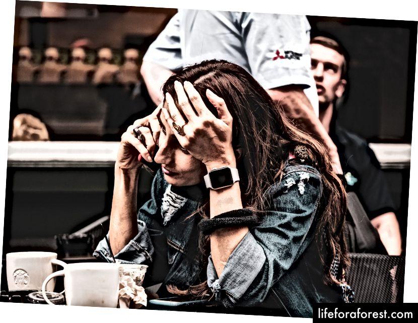 Người phụ nữ cầm điện thoại thông minh đang ngồi trên chiếc ghế màu đen trước bàn ăn của Kevin Grieve trên Bapt