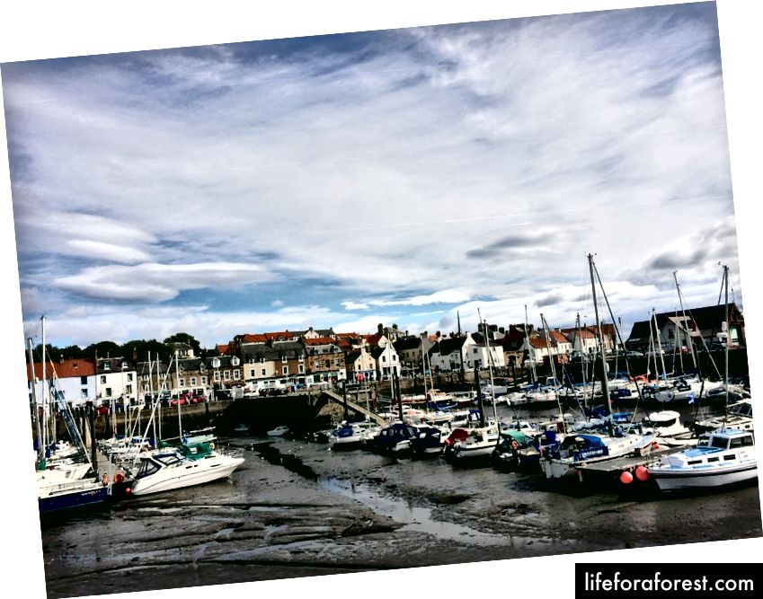 """Anstrutherio uostas; valtys prie paplūdimio yra įprastas reginys dėl dramatiškų """"Fife"""" potvynio pokyčių."""