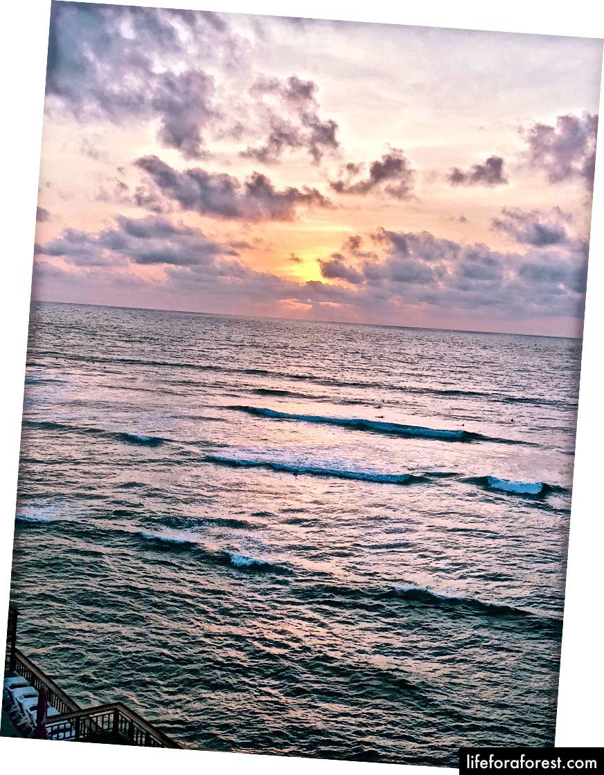 Sledování surfaři při západu slunce v Uluwatu