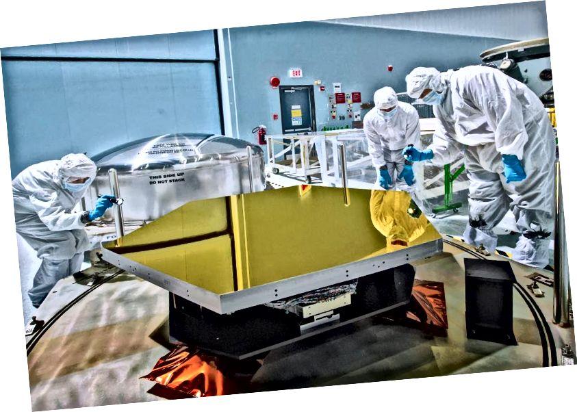 Техники и ученые проверяют одно из первых двух зеркал полета телескопа Уэбба в чистой комнате в Центре космических полетов имени Годдарда НАСА. Изображение предоставлено NASA / Chris Gunn.