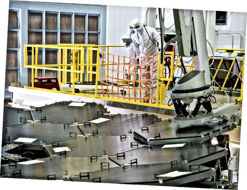 Установка 18-го и последнего сегмента первичного зеркала JWST. Черные крышки защищают позолоченные зеркальные сегменты. Изображение предоставлено NASA / Chris Gunn.