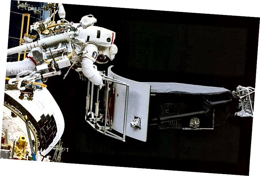 Астронавт Джеффри Хоффман снимает широкоугольную и планетарную камеру 1 (WFPC 1) во время операций по замене. Это было сделано во время первой миссии по обслуживанию Хаббла, которая привела к некоторым из величайших образов, которые когда-либо получало человечество, как с научной, так и с эстетической точки зрения. Изображение предоставлено NASA.