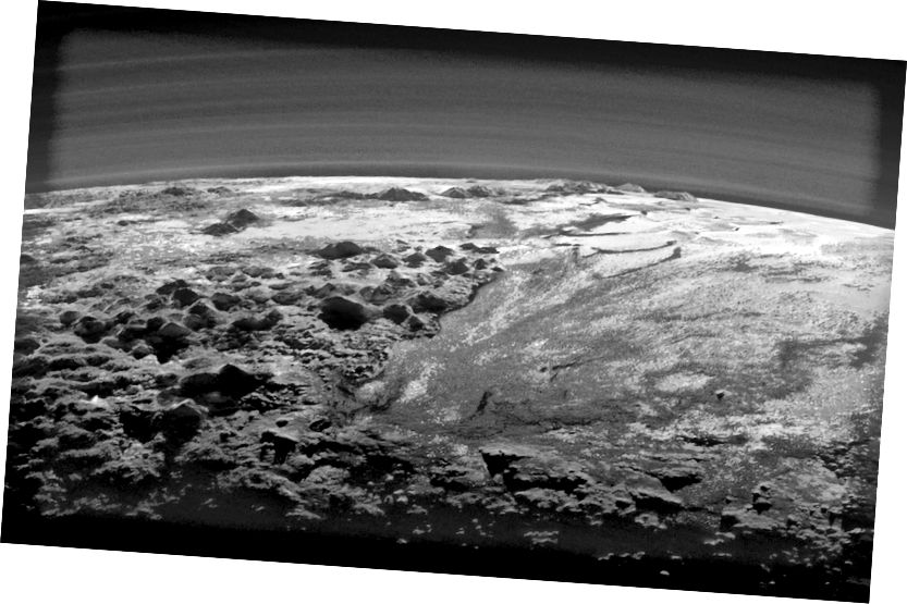 Svemirski brod New Horizons pogled na Pluton hrapave, ledene planine i ravnu ledenu ravnicu. Vidje se i više slojeva maglice atmosfere Plutona. Izvor: NASA