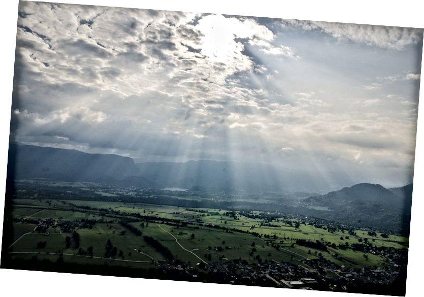 Grianghraf fearainn poiblí de bholg gréine, ó Pixabay ag https://pixabay.com/ga/sunbeams-sky-clouds-landscape-691635/.