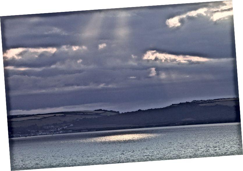 Grianghraf fearainn poiblí le húsáideoir Pixabay stux, trí https://pixabay.com/ga/landscape-sea-sunbeam-clouds-414551/.