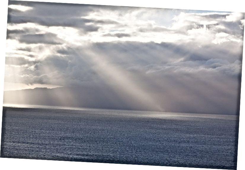 Grianghraf fearainn poiblí ó úsáideoir Pixabay stux, trí https://pixabay.com/ga/clouds-horizon-sunbeam-sea-ocean-571552/.