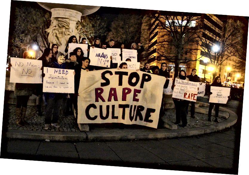 תמונה: מפגינים בשלטים עם חטיבת הביניים מול פסל, הבאנר הגדול ביותר בו נכתב