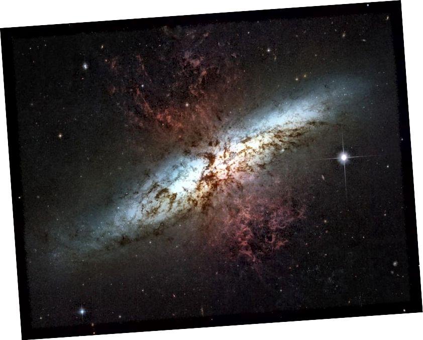 Die Starburst-Galaxie Messier 82, deren Materie wie von den roten Jets gezeigt ausgestoßen wird, hat diese Welle der aktuellen Sternentstehung durch eine enge Gravitationswechselwirkung mit ihrem Nachbarn, der hellen Spiralgalaxie Messier 81, ausgelöst (NASA, ESA, THE HUBBLE) HERITAGE TEAM (STSCI / AURA); ANERKENNUNG: M. MOUNTAIN (STSCI), P. PUXLEY (NSF), J. GALLAGHER (U. WISCONSIN))