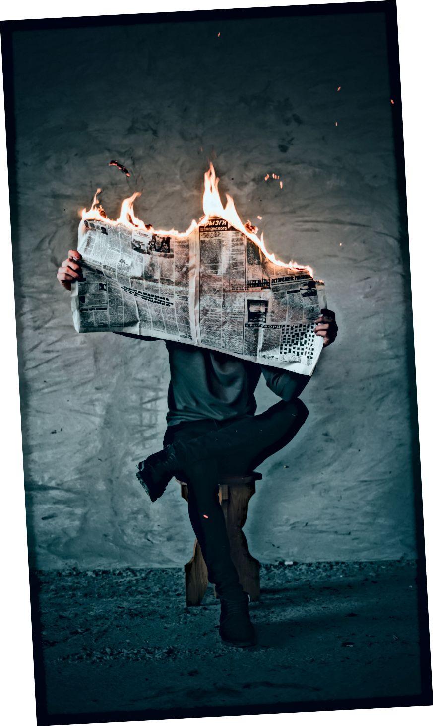 """""""Сюрреалистична фотография на човек, който чете вестници в огън, докато седи на табуретка"""" от Илия О'Донъл на Unsplash"""
