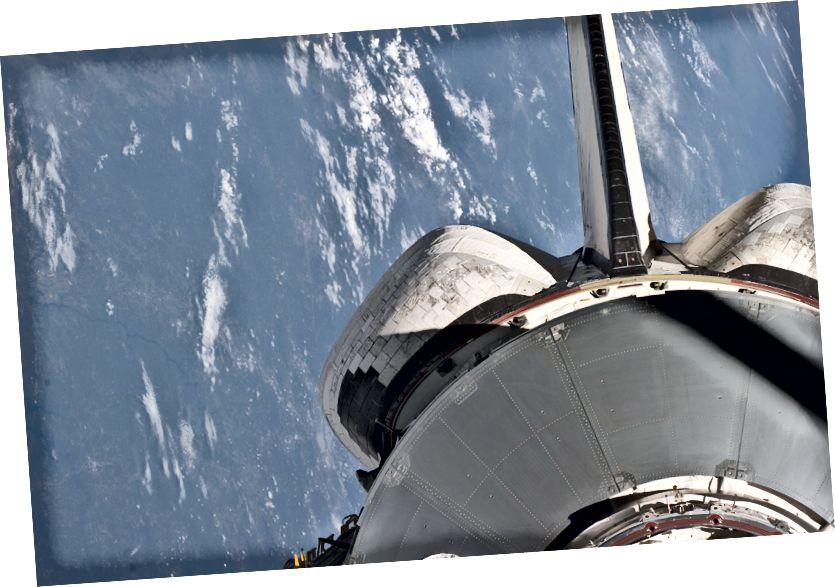 """""""Ein Teil des Raffaello-Mehrzwecklogistikmoduls, das mit Vorräten und Ersatzteilen für die Internationale Raumstation, dem vertikalen Stabilisator des Space Shuttles Atlantis und den Pods des Orbitalmanöversystems (OMS) gefüllt ist, ist vor einer überwiegend blauen Erdszene zu sehen Diese Ansicht wurde von einem der STS-135-Besatzungsmitglieder während des zweiten Aktivitätstages der Mission in der Erdumlaufbahn unter Verwendung von Fenstern auf dem Achterflugdeck des Raumfahrzeugs fotografiert. """" - Gutschrift: NASA"""