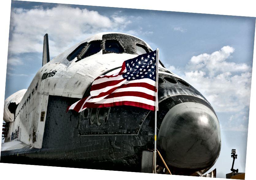 """""""Eine amerikanische Flagge weht im Wind vor dem Space Shuttle Atlantis auf der Runway 15 der Shuttle Landing Facility im Kennedy Space Center der NASA in Florida. Atlantis 'endgültige Rückkehr aus dem Weltraum um 5:57 Uhr (EDT) am 21. Juli 2011 beendete die 13-tägige STS-135-Mission mit einer Länge von 5,2 Millionen Meilen. Atlantis sicherte sich den Platz der Space-Shuttle-Flotte in der Geschichte und brachte das Space-Shuttle-Programm der Nation zum Abschluss. STS-135 lieferte Ersatzteile, Ausrüstung und Zubehör an die Internationale Raumstation. STS-135 war der 33. und letzte Flug für Atlantis, das 307 Tage im Weltraum verbracht hat, die Erde 4.848 Mal umkreiste und 125.935.769 Meilen zurücklegte. """" - Gutschrift: NASA"""
