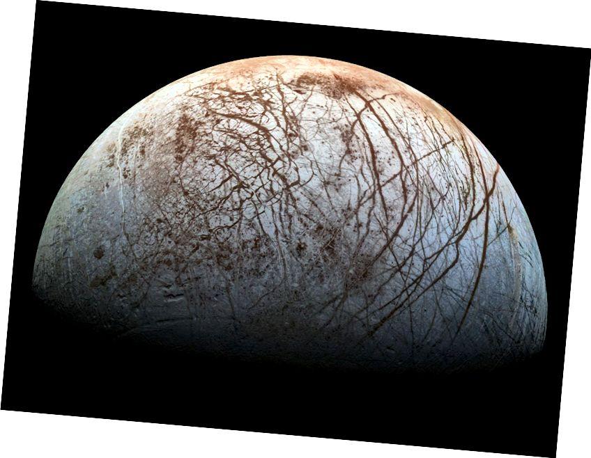 Найменшы луна Юпітэра, Еўропа, уцягнута ў прыгожыя чырванаватыя пражы. Выява з інстытута NASA / JPL-Caltech / SETI.
