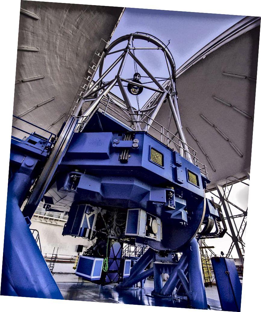 Máy ảnh hành tinh Gemini trên kính viễn vọng Gemini South. Trong ảnh, GPI bao gồm ba thành phần giống như hộp được gắn vào kính viễn vọng và treo gần sàn quan sát nhất. Các thành phần giống như hộp khác trên kính viễn vọng là các dụng cụ khác. (Đài thiên văn Manuel Paredes / Gemini / AURA)