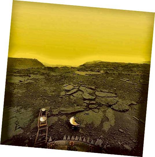 תמונה ממשית של פני השטח של ונוס שצולמה על ידי הנחתת הרוסית Venera 13, כובע העדשה השבור שלה בקדמת הבמה. עובדה מהנה: האווירה הוונוסית כל כך צפופה שהיא למעשה מכופפת אור נכנס בדומה להביט דרך מיכל מים, וזו הסיבה שכל התמונות על פני השטח של ונוס נראות