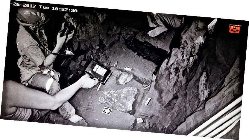 Elen Feuerriegel fotografira iskopnu jedinicu u podnožju prolaza kako Becca Peixotto (lijevo) osvjetljava scenu i Steven Tucker (gore) gleda. Izložena kost u jedinici uključuje djelomično zglobne dijelove ruku i zgloba, lubanje i rebra. Foto: John Hawks