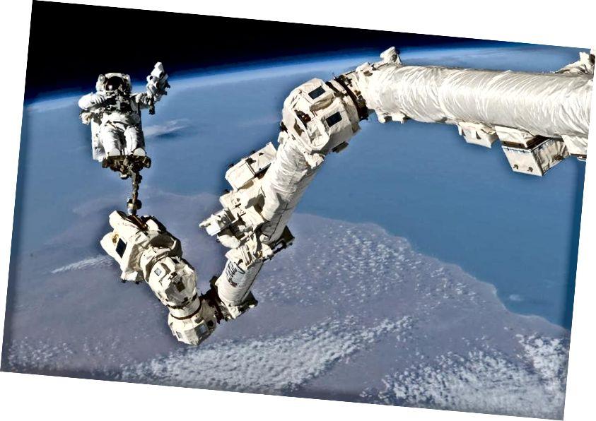 Астранаўт Стывен К. Робінсан, спецыяліст па місіі STS-114, які замацаваны на ножках на канадзе Canadarm2 Міжнароднай касмічнай станцыі, удзельнічае ў трэцяй сесіі звышвескулярнай дзейнасці місіі (EVA). Малюнак: НАСА.