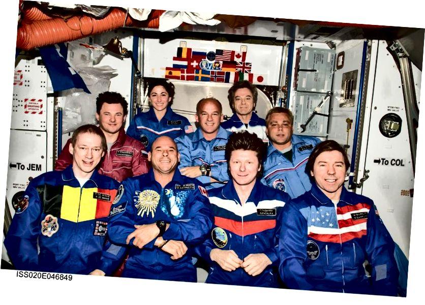 Ці можаце вы вызначыць, хто з удзельнікаў касмічнага палёту? Сюрпрыз: ён не ў чырвоным камбінезоне; ён у першым шэрагу, другі злева. Імідж: НАСА, члены экіпажа 20 і 21 членаў экіпажа і ўдзельнік касмічнага палёту Гай Лаліберт.