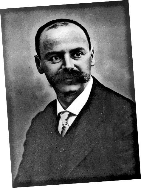 Ba réaltfhisiceolaí feiceálach Gearmánach é Karl Schwarzschild (1873–1916) agus úinéir ar ghruaig aghaidhe iontach. Mar thoradh ar a chuid oibre luatha ar choibhneasacht ghinearálta tuar poill dhubha. Grianghraf: Berlin-Brandenburgische Akademie der Wissenschaften - Cartlann