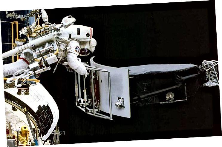 Astronavt Jeffrey Hoffman ilk Hubble xidmət missiyası zamanı dəyişiklik əməliyyatları zamanı Geniş Sahə və Planetary Kamera 1 (WFPC 1) çıxarır. Astronavtlar kosmosa səyahət hekayəsini ən yaxşı şəkildə izah edə bildikləri kimi, elm adamları da öz təcrübə sahələri haqqında hekayəni ən yaxşı şəkildə söyləyə bilərlər. (NASA)