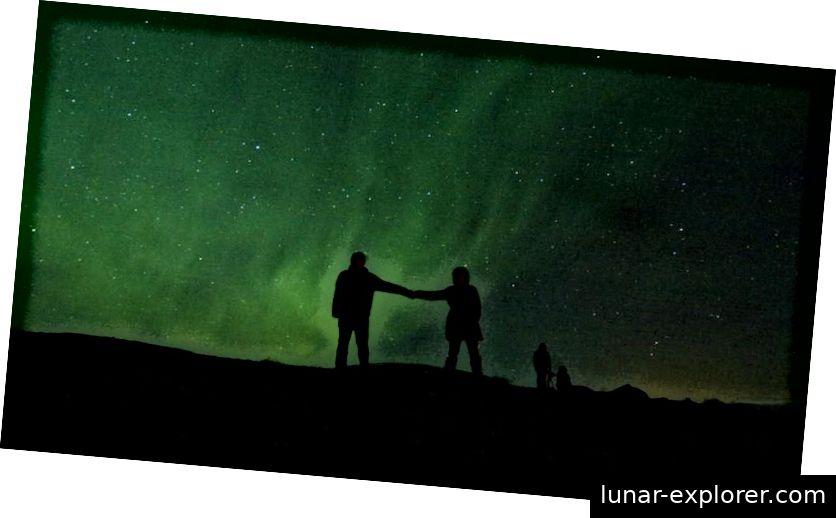 Silhouettiert gegen die Polarlichter, die in der Nähe der Pole auf der Erde entstanden sind, sind zwei Menschen sowie die Polarlichter selbst nur aufgrund der Materie im Universum und der grundlegenden Regeln der Physik möglich, nach denen sie sich hält. (BEN HUSSMAN / FLICKR)