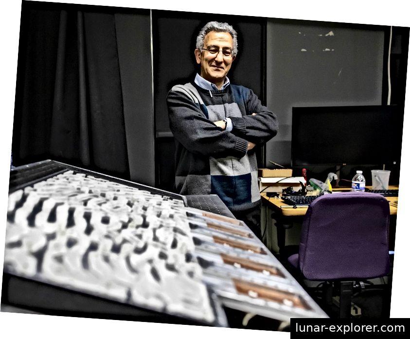 """Nader Engheta betrachtet das Metamaterial-Gerät seines Teams. Das """"Schweizer Käse"""" -Muster aus Kunststoff- und Luftlöchern ist präzise entworfen, um einen Teil einer bestimmten Integralgleichung darzustellen. (Foto: Eric Sucar)"""