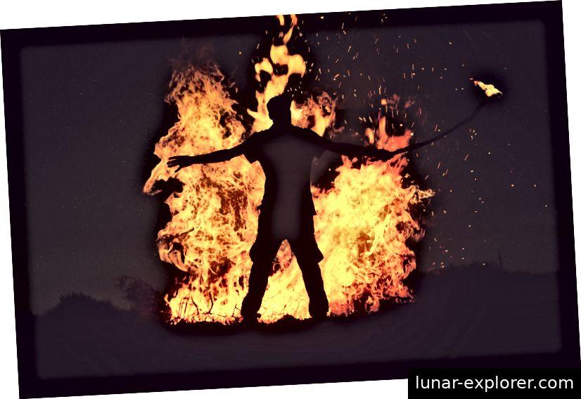 Man stößt mit einem Stock zu heftig gegen das Feuer. Foto von Mohamed Nohassi auf Unsplash