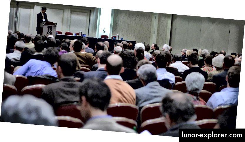 [BILD: Ein blasshäutiger männlicher Präsentationssprecher an einem Rednerpult vor einem weitgehend blasshäutigen männlichen Präsentationspublikum] Quelle